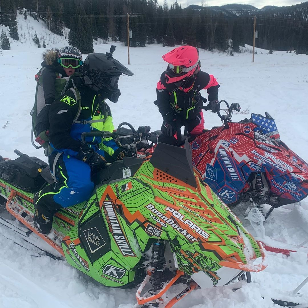 Cowboy rides his snowmobile with son Danger on his back