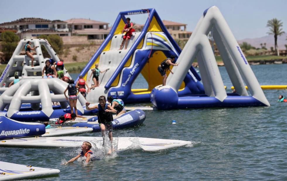People play at the recently opened Aqua Park at Lake Las Vegas in Henderson Thursday, June 11, ...