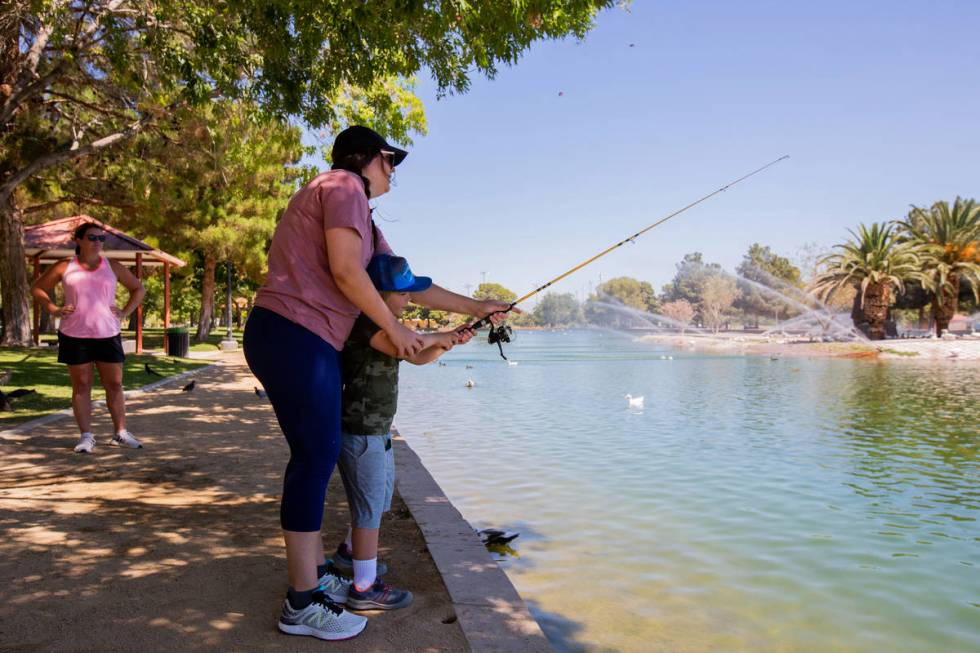 Emily Adinolfi watches as Kate Stone teaches her son Bergen Stone, 6, how to cast his fishing r ...
