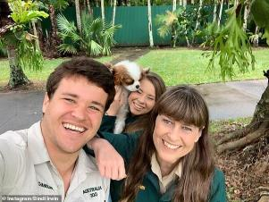Terri Irwin et al. posing for the camera: Glowing and gorgeous: She recently shared her baby's first sonogram with fans. And on Wednesday, pregnant Bindi Irwin was simply glowing in a selfie with her husband Chandler Powell and her mother Terri