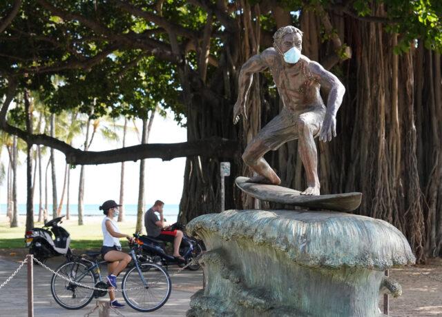 Masked surfing sculpture along Waikiki Beach on Kalakaua Avenue during COVID-19 pandemic.
