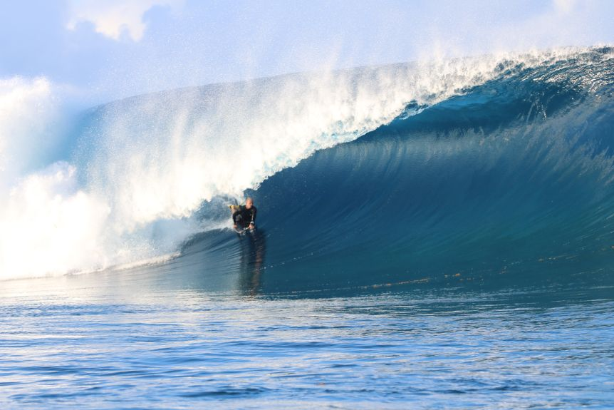 A bodyboarder on a huge wave, in the barrel of the wave with white water exploding behind him.