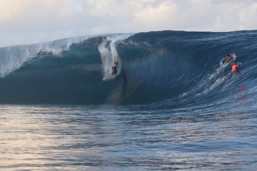 A man on a bodyboard dropping down the face of a huge wave.