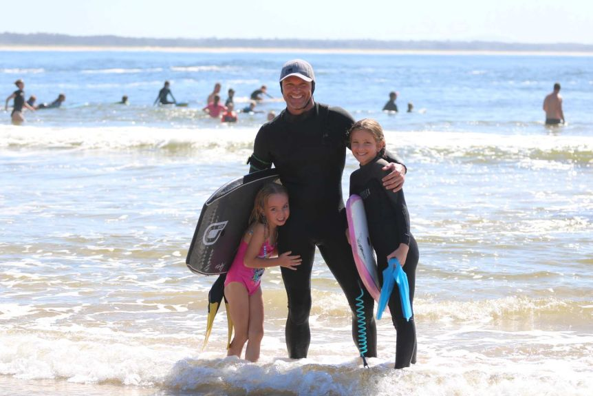 A man in a full wetsuit stands in the surf with his arms around his two young daughters.