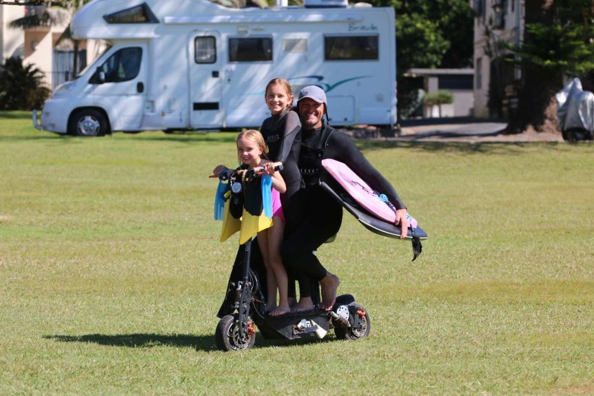 A man in a wetsuit sitting on a scooter, with two young girls in front of him, carrying bodyboards under his arm.