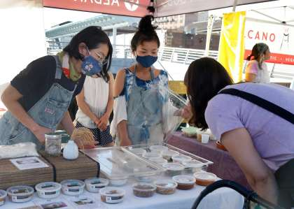 Mariko Grady (left) and Kana Weaver (center) helps a customer at the Aedan Fermented Foods stand at the Ferry Plaza Farmers Market in San Francisco, Calif. on Saturday, Sept. 26, 2020.